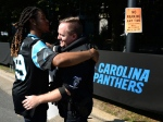 JaGerran Knight, of Charlotte, N.C., left, reaches out to hug a police officer at Bank of America Stadium, where people protest, prior to an NFL football game between the Minnesota Vikings and the Carolina Panthers in Charlotte, N.C., Sunday, Sept. 25, 2016. (Jeff Siner/The Charlotte Observer via AP)