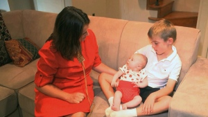 In this frame grab from video, taken Sept. 14, 2016, Sarah Gray with her son Callum, 6, and infant daughter Jocelyn in their Washington home. (AP / Rick Gentilo)