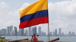 A couple takes selfies under a Colombian flag in Cartagena, Colombia, Monday, Sept. 26, 2016. (AP Photo/Fernando Vergara)