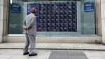 A man walks past an electronic stock board of a securities firm in Tokyo, Tuesday, Sept. 27, 2016. (AP / Eugene Hoshiko)