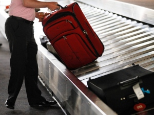 A traveller collects his bag from a luggage carousel at Philadelphia International Airport on June 13, 2011. (AP / Matt Rourke)