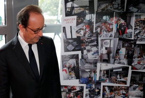 French President Francois Hollande walks past photographs of the devastated printing plant after the attack, as the plant reopens Thursday Sept. 29, 2016 in Dammartin-en-Goele, north of Paris. (Philippe Wojazer, Pool photo via AP)