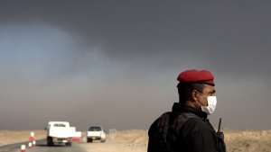 A member of the Iraqi special forces guards a checkpoint near the village of Awsaja, Iraq, as smoke from fires lit by Islamic State militants at oil wells and a sulphur plant fill the air on Saturday, Oct. 22, 2016. U.S. military officials say that a fire at the sulfur plant in northern Iraq is creating a potential breathing hazard for American forces and other troops at a logistical base south of Mosul. (AP Photo/Adam Schreck)