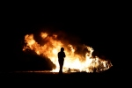 """A man stands by some flames near a makeshift migrant camp known as """"the jungle"""" near Calais, northern France, Sunday Oct. 23, 2016. French authorities say the closure of the slum-like camp in Calais will start on Monday and will last approximately a week in what they describe as a """"humanitarian"""" operation. (AP Photo/Emilio Morenatti)"""