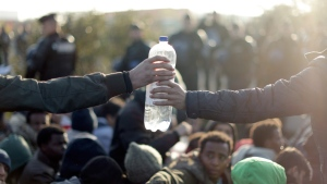 Migrants share a bottle of water at 'the jungle' near Calais, France, on Oct. 24, 2016. (Matt Dunham / AP)