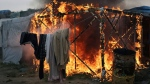 """A tent burns in the makeshift migrant camp known as """"the jungle"""" near Calais, northern France, Wednesday, Oct. 26, 2016. Firefighters have doused several dozen fires set by migrants as they left the makeshift camp where they have been living near the northern French city of Calais. (AP Photo/Thibault Camus)"""