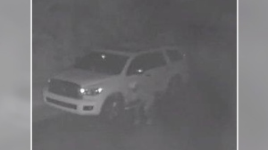 Still image from grainy surveillance video that shows a man in a hoody as he bends down, and slashes two tires of a white SUV. (Gatineau Police)