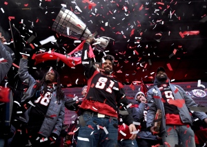 Ottawa RedBlacks Patrick Lavoie raises the Grey Cup over his head during a rally at Aberdeen Square, celebrating the team's victory over the Calgary Stampeders, Tuesday, Nov. 29, 2016 in Ottawa. (Justin Tang / THE CANADIAN PRESS)