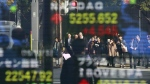 People are reflected on the electronic stock indicator of a securities firm in Tokyo on Monday, Dec. 5, 2016. (AP / Shizuo Kambayashi)