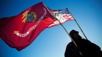 Marine Corps veteran and Northern Paiute and Pit River Native American Audie Noneo, of Susanville, Calif., holds the Marine Corps flag at the Oceti Sakowin camp where people have gathered to protest the Dakota Access oil pipeline in Cannon Ball, N.D., Sunday, Dec. 4, 2016. (AP Photo/David Goldman)