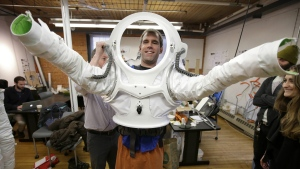 In this Monday, Dec. 5, 2016 photo, Andrzej Stewart, the chief engineering officer on a year-long Mars simulation mission that ended in August, puts on a new space suit at the Rhode Island School of Design (RISD) in Providence, R.I. (AP / Steven Senne)