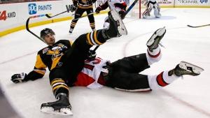 Pittsburgh Penguins' Justin Schultz (4) falls on top of Ottawa Senators' Zack Smith in the second period of an NHL hockey game in Pittsburgh, Monday, Dec. 5, 2016. (Gene J. Puskar/AP Photo)