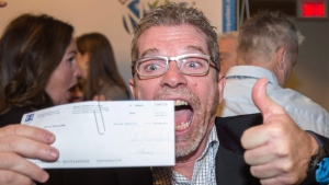 Lottery winner Gilles Leprohon celebrates after receiving his cheque, Thursday, January 12, 2017 in Montreal. Twenty eight members of the same Quebec family are sharing a $60-million lottery win, the biggest prize ever awarded by Loto-Quebec. (Paul Chiasson/THE CANADIAN PRESS)