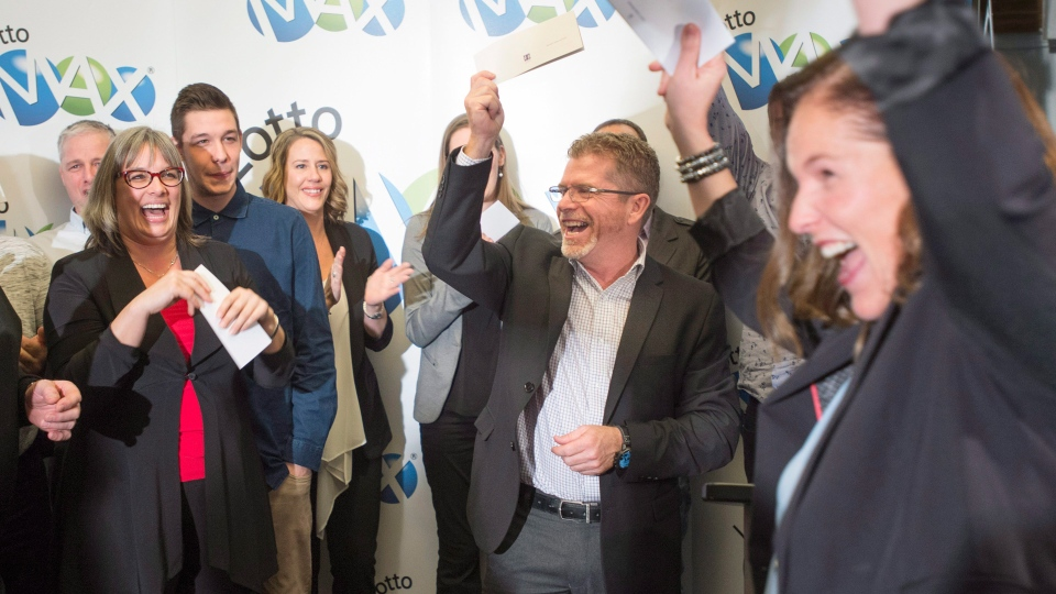 Lottery winners celebrate after receiving their cheques, Thursday, January 12, 2017 in Montreal. Twenty eight members of the same Quebec family are sharing a $60-million lottery win, the biggest prize awarded ever by Loto-Quebec. (Paul Chiasson/THE CANADIAN PRESS)