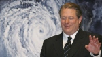 """In this Jan. 15, 2007 file photo, former U.S. Vice President Al Gore acknowledges spectators in front of a poster of his starring documentary film """"An Inconvenient Truth"""" on global warming before its screening during the Japan Premier at a theater in Tokyo. (AP / Koji Sasahara, File)"""
