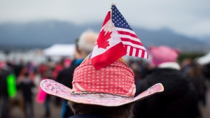 A woman sports Canadian and U.S. flags on her hat during a women's march and protest against U.S. President Donald Trump, in Vancouver, B.C., on Saturday January 21, 2017. (The Canadian Press/Darryl Dyck)