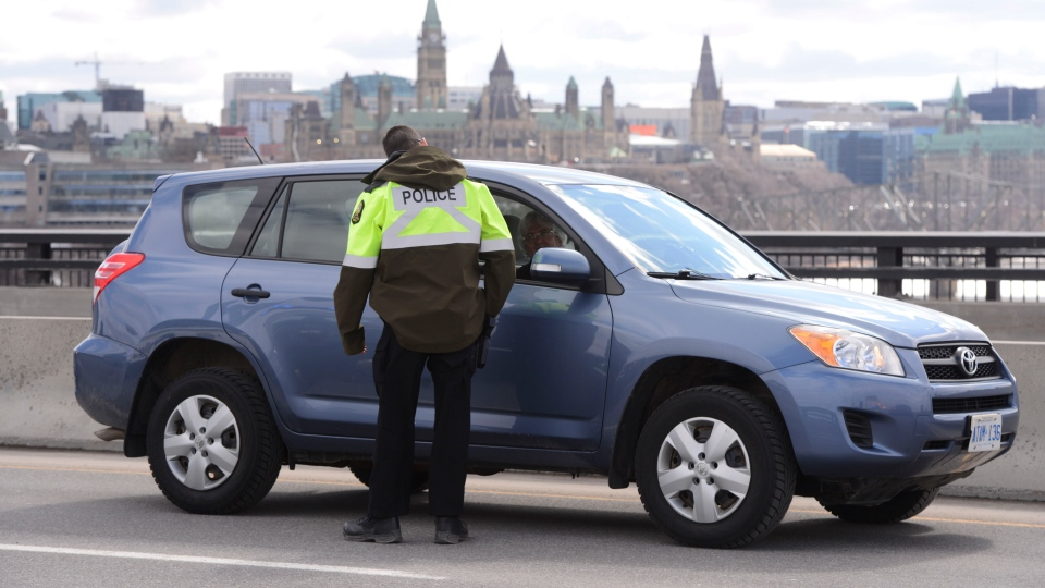 Quebec police officers stop traffic entering QC