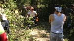 Residents use chainsaws and other tools to help clear a rock blocked by fallen trees in Norway Lake on Tuesday, July 24, 2012.